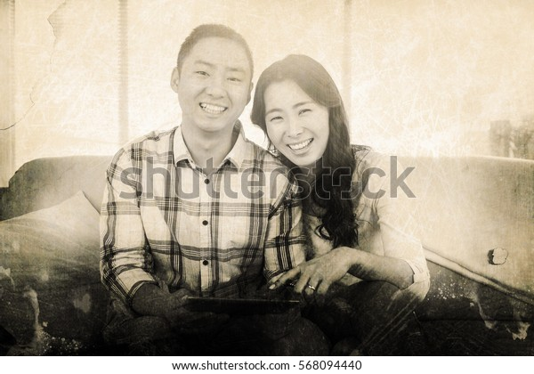 Grey background against young happy couple holding digital tablet