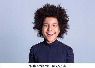 Grey background. Dark-haired African American little person being extremely happy during photoshoot while showing strong white teeth