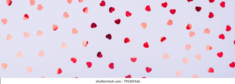 Grey background with red glitter heart confetti. Valentine day concept. Trendy minimalistic flat lay design background. Horizontal, banner format