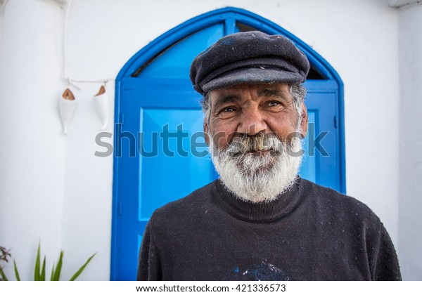 Grey bearded man posing in between of painting doors in the town of Sidi Bou Said. 07/MAY/2016