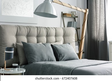 Grey bed with quilted headboard and big wooden lamp