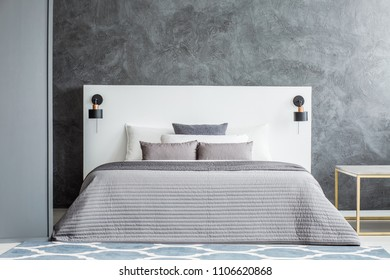 Grey bedsheets on bed with white bedhead against concrete wall in monochromatic bedroom interior