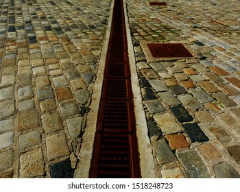 grey & black cube granite cobblestone pavement abstract of rectangular shapes loosely set. cement mortar joints. street & walkway paving design concept. stone texture. perspective. rusty steel trench.