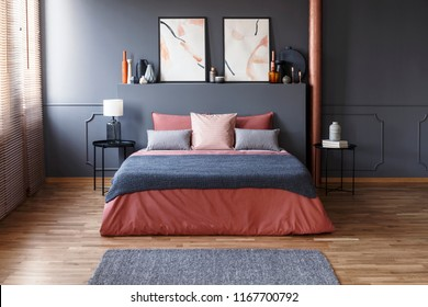 Grey blanket on pink bed against the wall with poster in modern bedroom interior