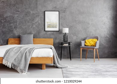 Grey blanket and pillow on the wooden bed with white bedding in stylish bedroom interior with concrete wall