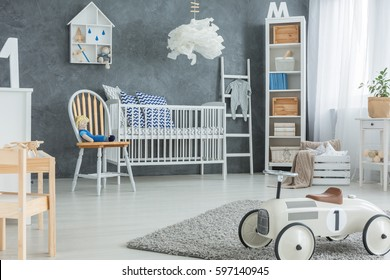 Grey boy room with white cot, bookcase and rug