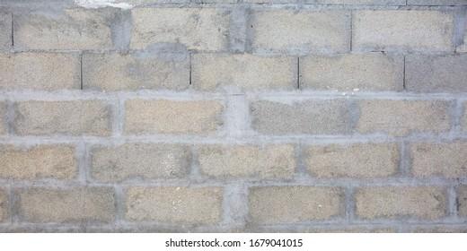 Grey brick cinderblocks wall closeup texture concrete block background
