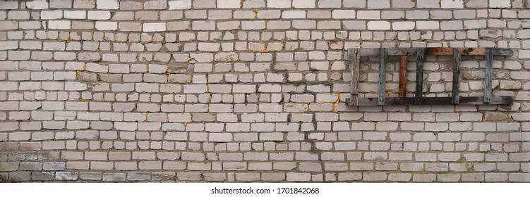 Grey brick wall with traces of destruction and dirty texture