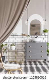 Grey cabinet with washbasin in modern bathroom interior with drapes and mirror. Real photo