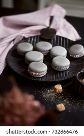 Grey cakes macaroons on the dark surface of the table, next to a spoon and sugar bowl with brown sugar.