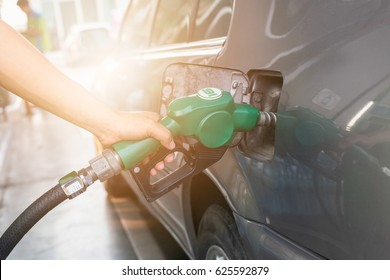 Grey car at gas station being filled with fuel on thailand