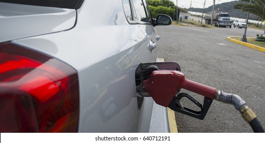 Grey car at gas station being filled with fuel.