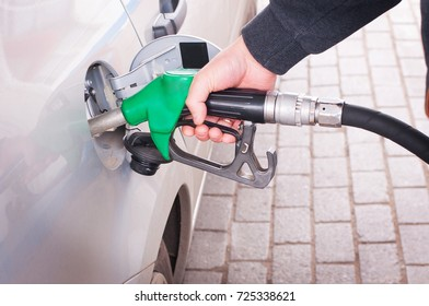 Grey car at gas station being filled with fuel