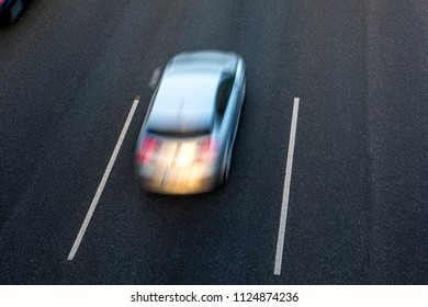 Grey car runs fast in the highway by the central lane at sunset. Top view and copy space in the other lanes.