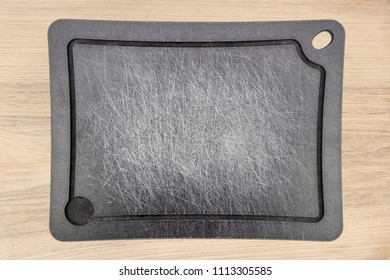 grey carved stripped used meat cutting board on wooden backgournd