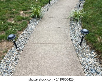 grey cement path with solar lights and grasses