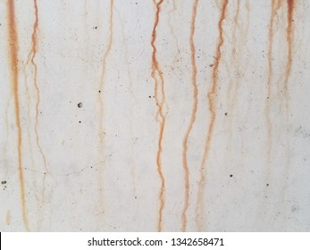 grey cement wall with red rust dripping down