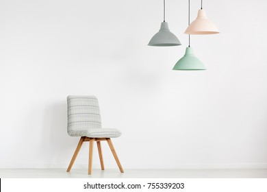 Grey chair against white wall with copy space in empty room with peach, mint and grey lamp