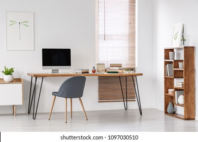 Grey chair at desk with computer monitor in minimal workspace interior with poster. Real photo