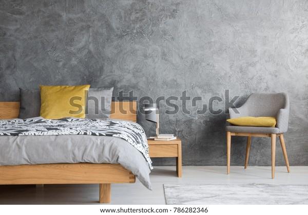Graustuhl und Lampe auf Holzhintergrund im dunklen Schlafzimmer mit Beton und gelbem Kissen auf dem Bett