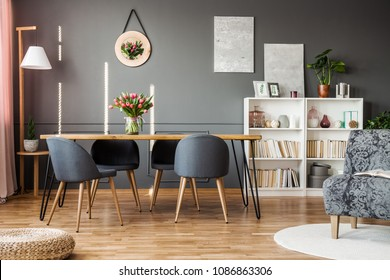 Grey chairs at wooden table with red tulips in dining room interior with books on shelves