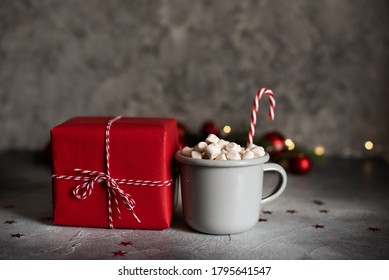 Grey Christmas mug with marshmallows and gifts in red packaging.