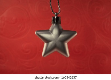 grey christmas star ornament on red background
