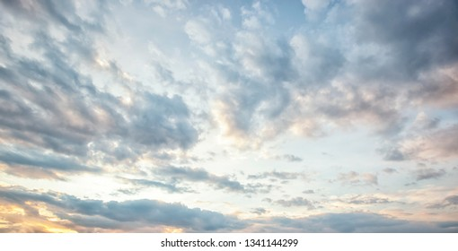 Grey clouds in the blue sky and rays of the sun