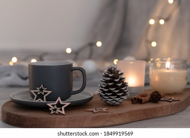 Grey coffee cup on a wooden board, cone, candles, cinnamon sticks, fairy lights and soft grey blanket together in a cozy autumn decoration with glitter wooden stars. Hygge concept. Soft focus bokeh.