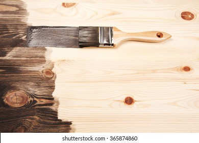 Grey color painting on wooden table or fence or wall, or flour, use for home decorated. House renovation. Half - painted surface. Smear of paint brush.