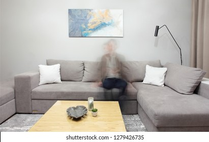 Grey corner couch with three pillows standing in bright living room interior with painting and carpet.Lightning on.Artistica shot with ghost