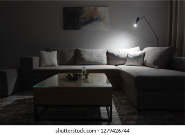Grey corner couch with three pillows standing in bright living room interior with painting and carpet.Dramatic Lightning.