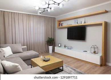 Grey corner couch with three pillows standing in bright living room interior with painting and carpet.Lightning on