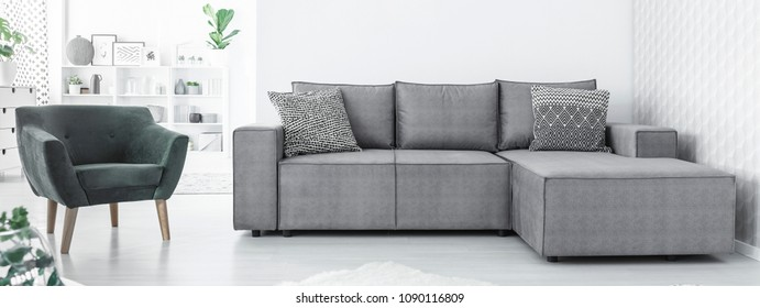 Grey corner sofa with two black and white cushions and green chair standing in white Scandinavian open space interior