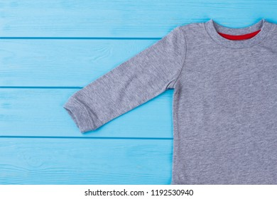 Grey cotton baby t-shirt on wood. Close up. Blue background.