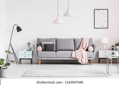 Grey couch with blanket between cabinets in living room interior with poster and lamps. Real photo