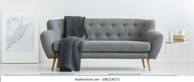 Grey couch with dark blanket standing in bright interior with metal table and simple poster