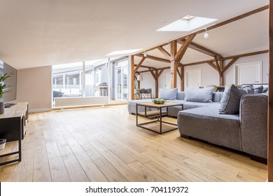 Grey couch set and coffee table on wooden floor in spacious living room with view on terrace