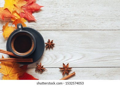 Grey cup of coffee, cinnamon, anise, red and yellow maple leaves on white wooden table. Autumn background concept. Fall menu, expresso, coffee shop, break, copy space, page