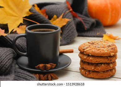 Grey cup of coffee, stack of cookies, spices, scarf, yellow maple leaves, orange pumpkin on white wooden table. Autumn menu concept. Fall, expresso, cinnamon, side view