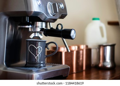 Grey cup with white heart detail under an stainless steel espresso machine. Steam wand and group head visible. Tea, coffee and sugar caddies in the background with Milk and milk jug.