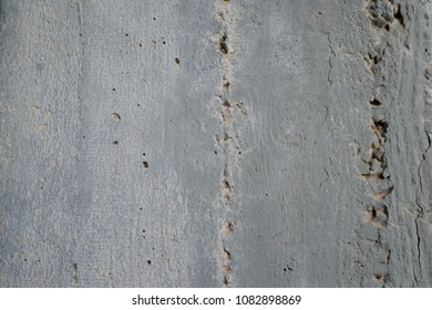Grey dirty skratched wall with vertical lines and cracks