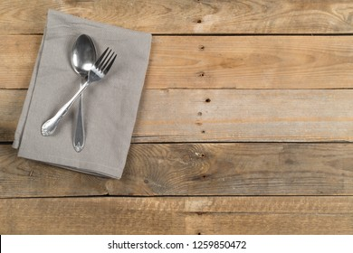 Grey dishcloth with fork and spoon silverware on brown rustic wooden plank table flat lay top view from above with copy space