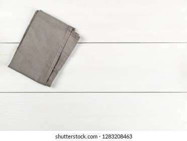 Grey dishcloth on white wooden plank table flat lay top view from above with copy space
