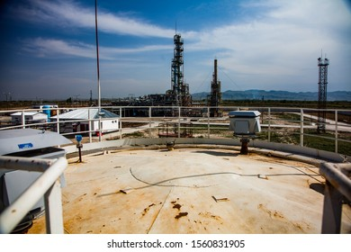 Grey distillation column on bright sun at a blue sky with clouds on oil refinery plant in a desert.