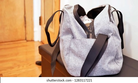 grey duffel gym bag for sport and fitness, an unbranded open bag full of clothes on the table with room background and copy space.