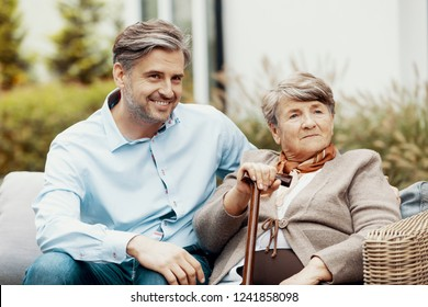 Grey elder lady with walking cane sitting in the garden with her handsome oldest son