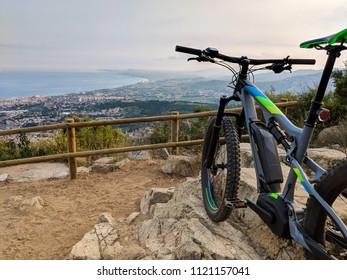 Grey electric mountain bike standing on top of mountain overlooking the ocean and valley near Barcelona Spain