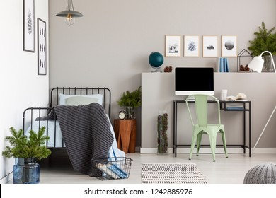 Grey elegant bedroom with single metal bed with blue bedding and dark grey blanket next to home office in teenager bedroom