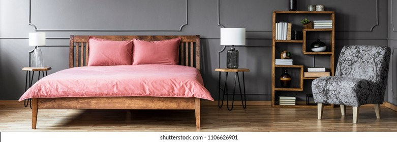 Grey floral armchair and wooden rack with books and decor standing in dark bedroom interior with pink sheets on bed placed between two hairpin tables with lamps